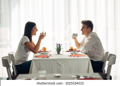 Happy couple at restaurant eating lunch.Talking over meal.Hotel full board,all inclusive stay.Travel, date,food,lifestyle.Smiling people having healthy breakfast.Food review.Manners at the table