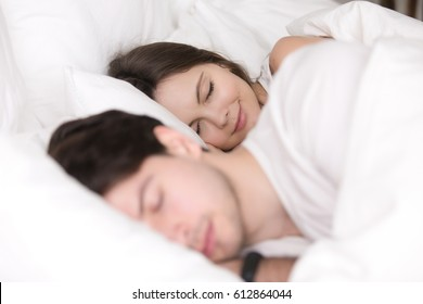 Happy couple resting together, enjoying soft bed and pleasant good dreams, beautiful girl smiling while sleeping with her boyfriend or husband between the sheets at home