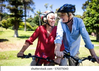 Happy couple riding a bicycle in park on a sunny day