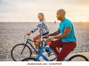 happy couple riding bikes at santa monica beach together