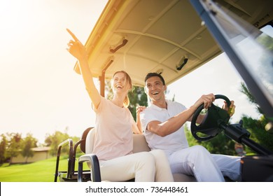 Happy couple riding a golf cart. A man in a white suit is sitting at the wheel and driving a golf car, a woman in a light suit is sitting beside him