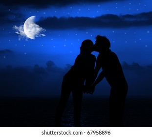 Happy couple romantically kissing at night under moonlight