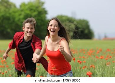 Feliz pareja corriendo y coqueteando entre la hierba en un campo verde de amapola en primavera