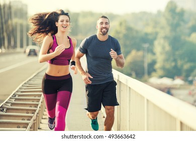 Happy couple running over the bridge. Living healthy lifestyle.