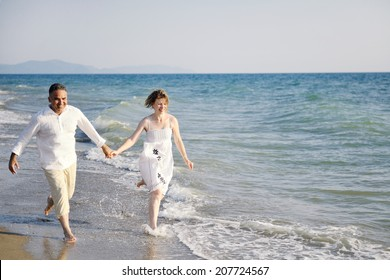 happy couple running through sea waves on the beach at sunset