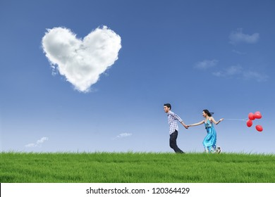Happy couple is running together in green field while holding red balloons