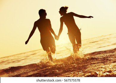 Happy couple runs to sunset sea. Silhouette tropical vacations concept