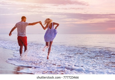 Happy couple runs in wave splashes at romantic sea sunset