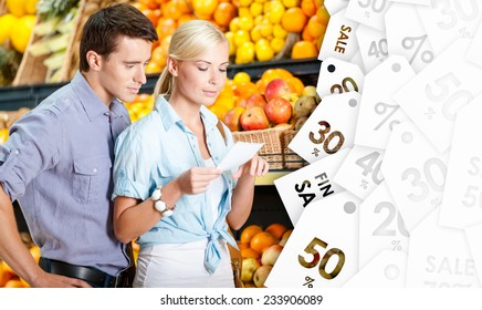Happy couple with sale coupons decides what to buy