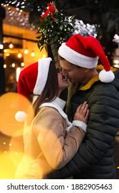 Happy couple in Santa hats kissing under mistletoe bunch outdoors, bokeh effect