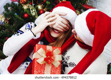 Happy Couple in Santa's Hat with Christmas and New Year Gift at Home
