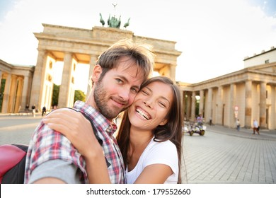 Happy couple selfie selfportrait in front of Brandenburg Gate or Brandenburger Tor, Berlin, Germany. Beautiful young multiracial travel couple having fun on Europe vacation. Asian woman, Caucasian man