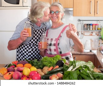 Happy couple of senior people enjoying the juice fruit just made. Husband kisses the wife. Wooden table with a large group of colorful fruits and vegetables. Healthy eating