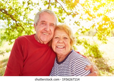 Happy couple of seniors in embrace in nature in summer