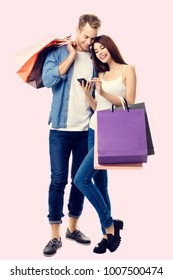Happy couple with shopping bags, and cellphone, standing close to each other with smile. Caucasian models in love, holiday sales, shop, retail, consumer concept.