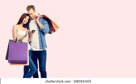 Happy couple with shopping bags, and cellphone, with copyspace empty area for slogan or advertising text message, over pink background. Love, holiday sales, shop, retail, consumer concept studio shot.