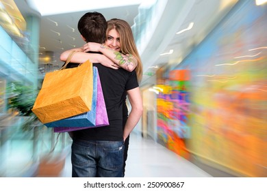 Happy couple with shopping bags in the mall