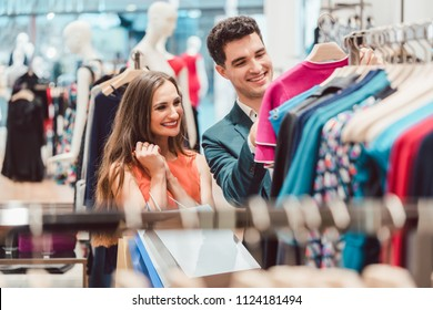 Happy couple shopping for fashion items in high end boutique
