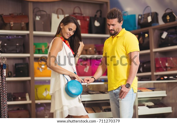 Happy couple in shopping mall visit store with leather bags