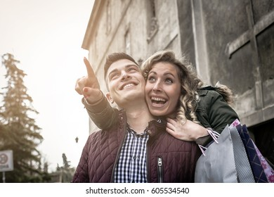 Happy couple shopping together and having fun. Girl showing something to her boyfriend.