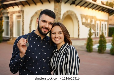 Happy couple showing keys of new home. Happy man and woman holding key of house. Home - the dream of a young couple. Purchase, rent, loan or real estate loan