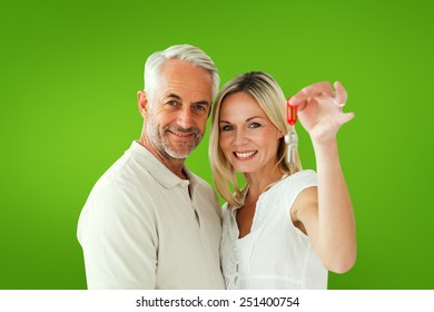 Happy couple showing their new house key against green vignette