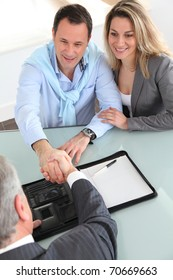Happy couple signing purchase contract with real-estate-agent