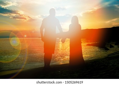 happy couple silhouette by the Greek sea on the shore background