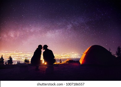 Happy couple in silhouette kissing near campfire and orange tent. Night sky with Milky Way stars and city lights at background.