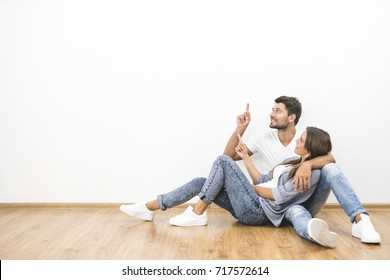 The happy couple sit and gesture on the background of the white wall