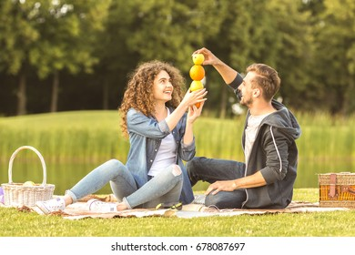 The happy couple sit the grass and hold fruits