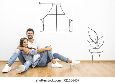The happy couple sit on the floor near illustrations on wall