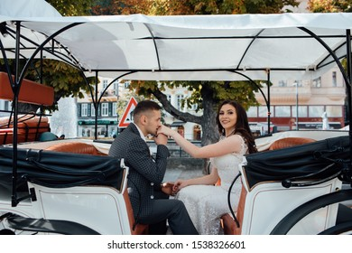 Happy couple sits are in coach with horse in city. Guy kisses girl's hand. Handsome guy in suit and girl in white dress. Beautiful couple enjoying time spending with each other.  Fashion photo.