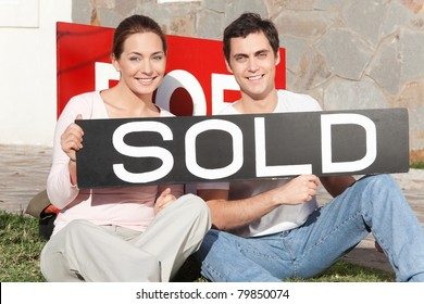 Happy couple sitting against their new house with sold sign