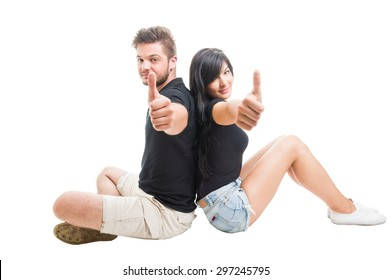 Happy couple sitting back to back and showing like or thumbs up gesture