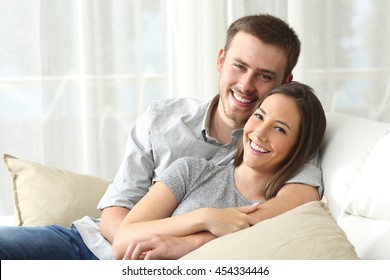 Happy couple sitting in a comfortable couch in the living room and looking at you at home
