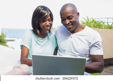 Happy couple sitting in garden using laptop together on a sunny day