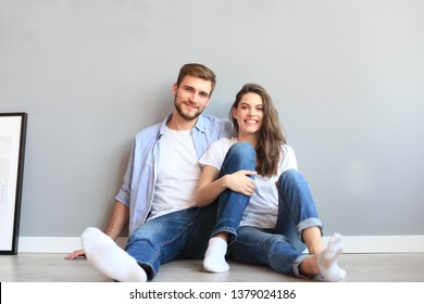 The happy couple sitting on the background of the gray wall.