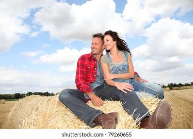 Happy couple sitting on bale in farmland
