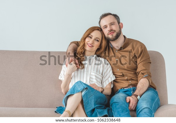 happy couple sitting on couch and smiling at camera on grey