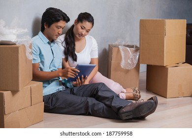 Happy couple sitting on floor using tablet in their new home