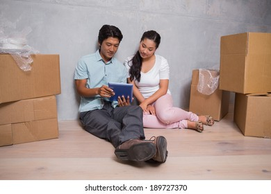 Happy couple sitting on floor using tablet surrounded by boxes in their new home