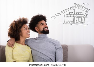 Happy Couple Sitting On Sofa Thinking Of Getting Their Own House