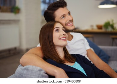 happy couple sitting on the sofa looking up with a smile as they are thinking about something