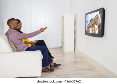 Happy Couple Sitting On Sofa Watching Television