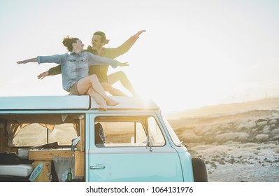 Happy couple sitting on top of minivan roof at sunset - Young people having fun on summer vacation traveling around the world - Travel, love, van lifestyle and freedom concept - Focus on bodies