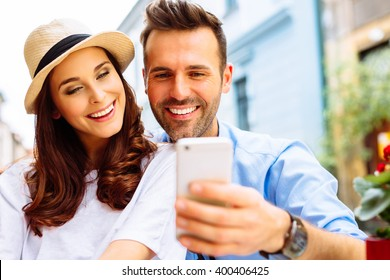 Happy couple sitting outdoors in cafe, looking at the phone