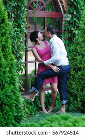 happy couple sitting outdoors, hugging and holding onto each other kissing against a brick wall with large Windows, overgrown greenery