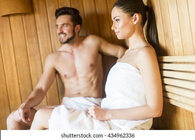 Happy couple sitting in sauna leaning to each other