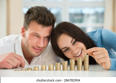 Happy Couple Sitting With Stacks Of Golden Coins Over Table At Home